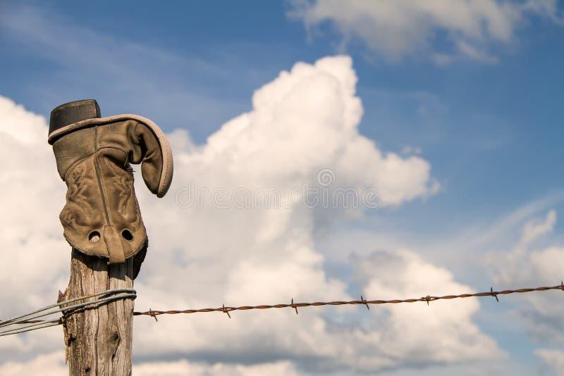Ботинок ковбоя на столбе загородки стоковая фотография
