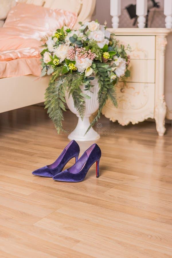 Ботинок пурпурной замши высокий накрененный на предпосылке спальни Женские ультрамодные ботинки для партии или романтичного обеда стоковое фото rf