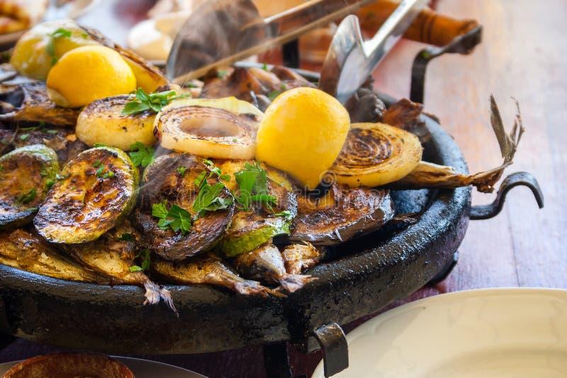 Болгарская нагревательная плита с рыбами, courgettes и луками стоковое изображение rf