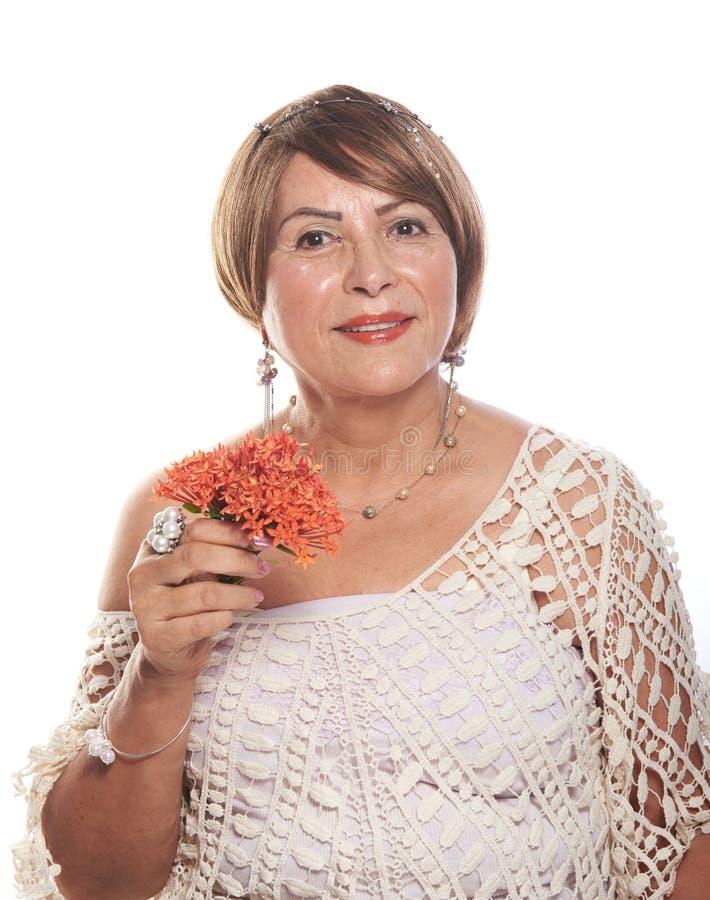 Более старая дама представляя с цветками стоковая фотография