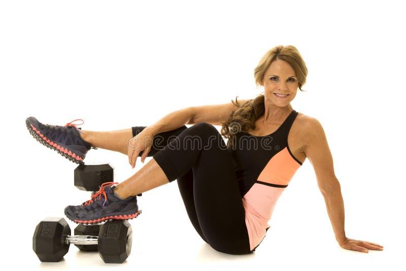 Более старая женщина кладя ноги на весы подготовляет на колене стоковые фото