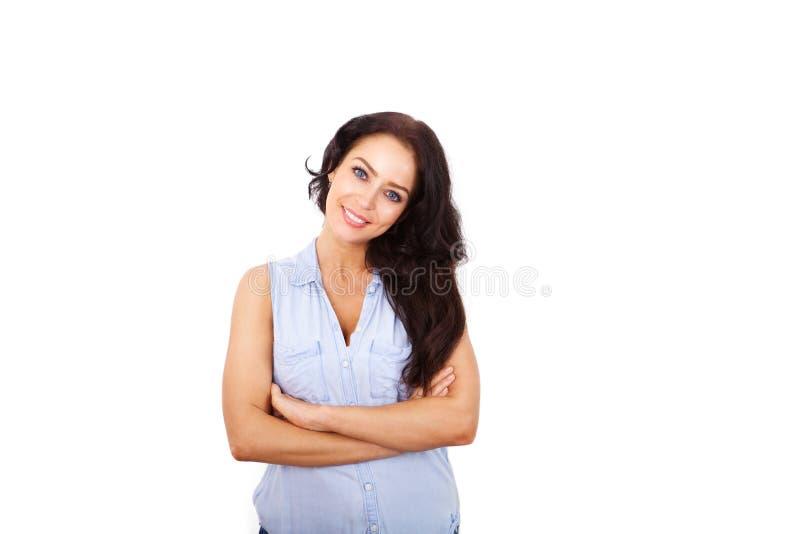 Более старая женщина усмехаясь с оружиями пересекла против белой предпосылки стоковые изображения rf