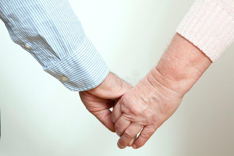 Более старые пары держа руки на белой предпосылке стоковая фотография