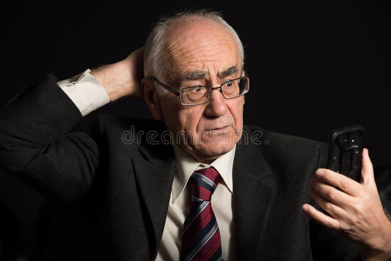 Более старый бизнесмен с умным телефоном стоковые фото