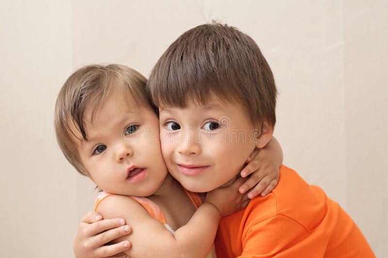 Более старый брат и более молодая сестра обнимая портрет стоковая фотография