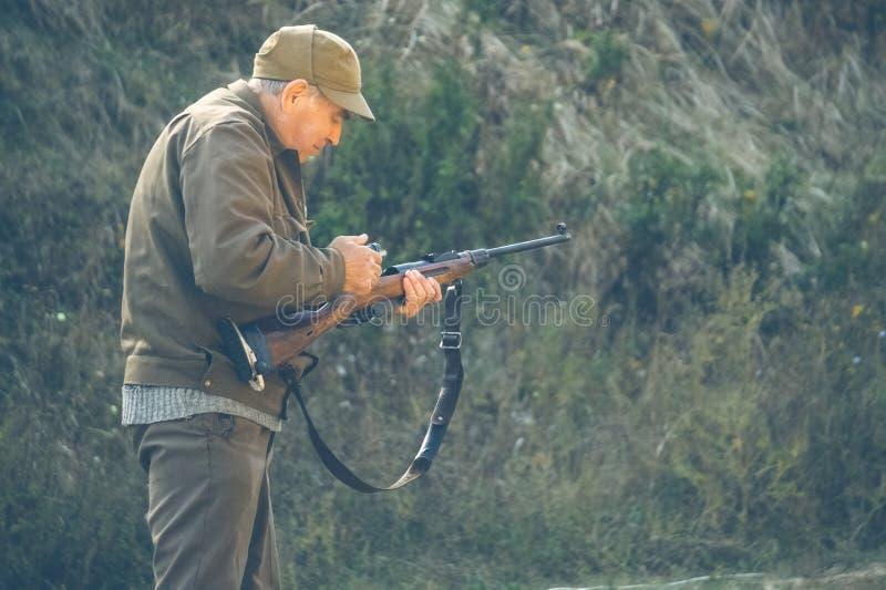 Более старый охотник взводит курок оружию стоковое фото rf