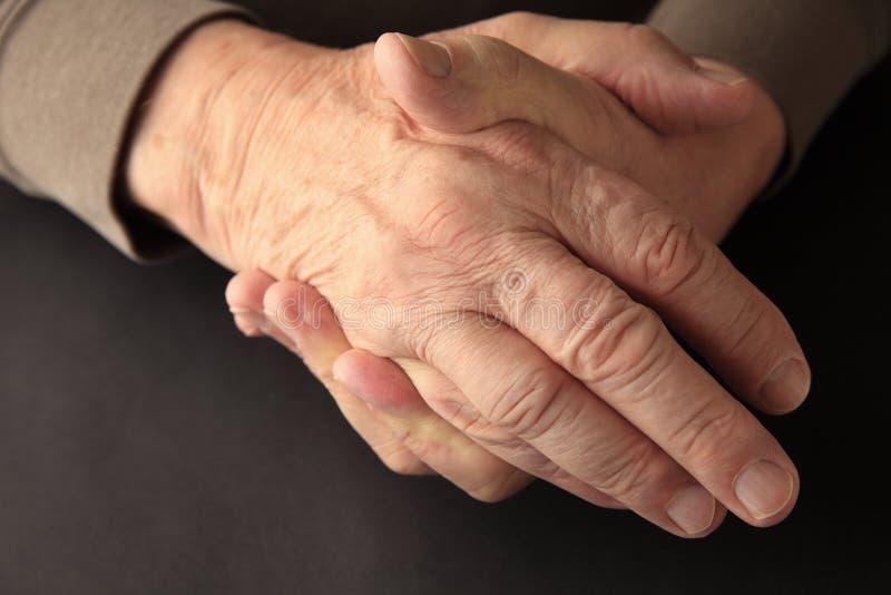 Более старый человек держа его онемелое hand стоковые изображения rf
