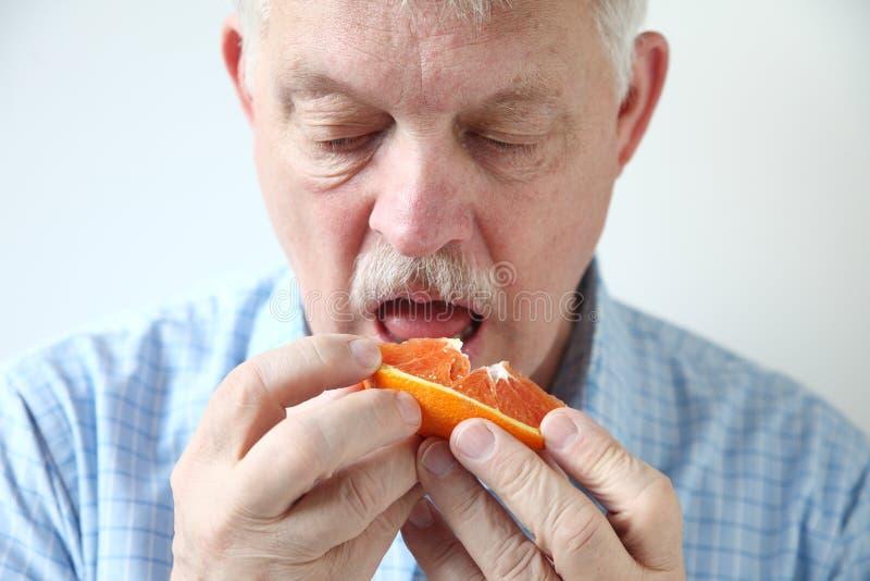 Более старый человек есть апельсин стоковая фотография