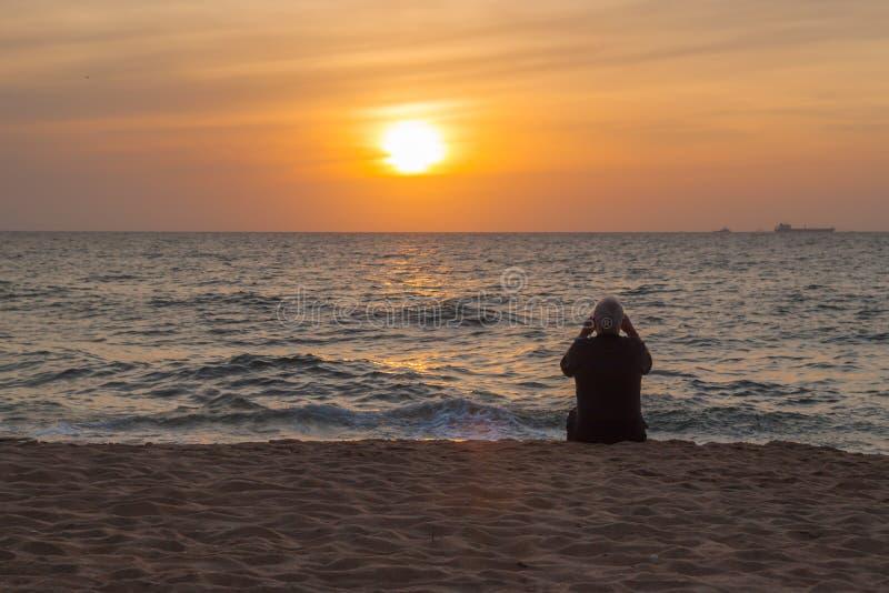 Более старый человек наблюдая на заходе солнца океана стоковые изображения rf