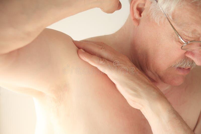 Более старый человек проверяет soreness в плече стоковое изображение