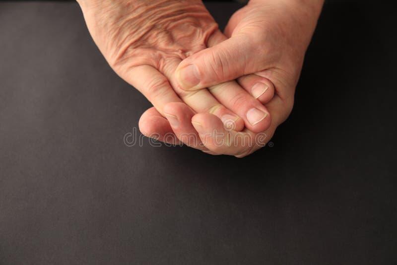 Более старый человек сжимает его онемелые пальцы стоковые изображения