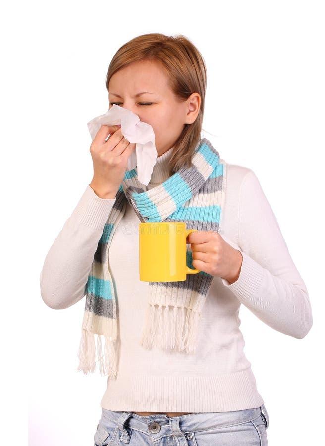 Больная женщина с чашкой чаю чихая в изолированной ткани стоковое фото rf