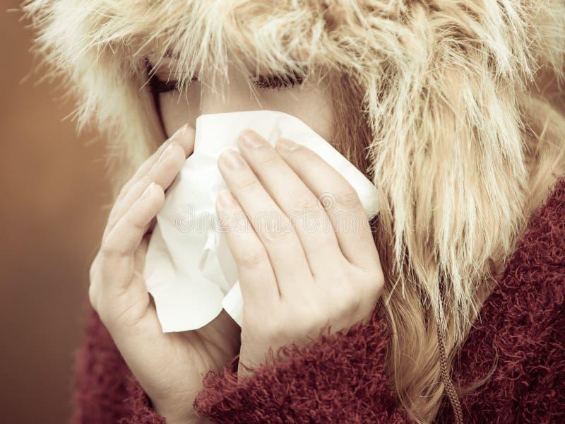 Больная женщина чихая в ткани внешней стоковое фото rf