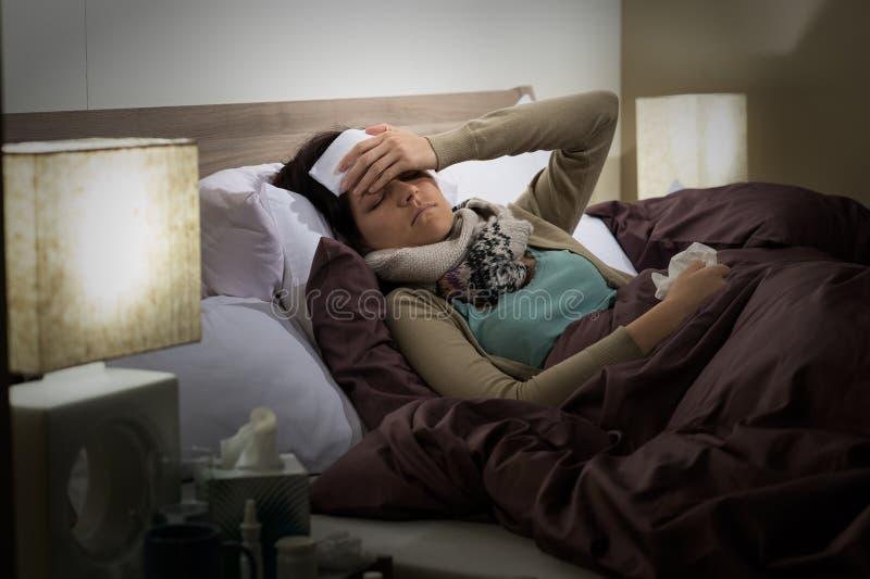 Больной молодой женщины лежа в холоде кровати стоковое изображение rf