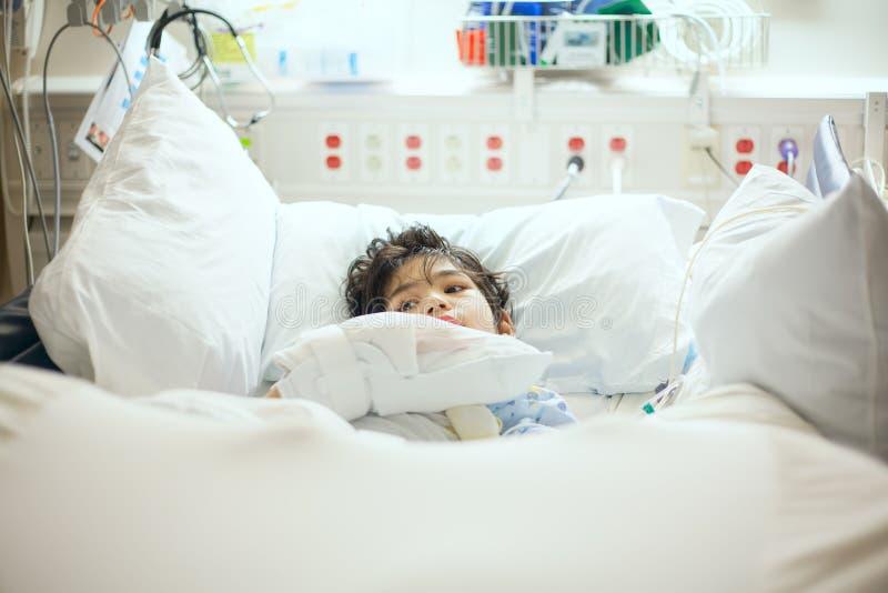 Больной неработающего мальчика лежа в больничной койке стоковые фото