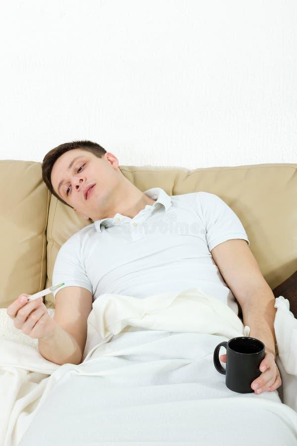 Больной человек лежа на температуре софы измеряя с термометром стоковые изображения