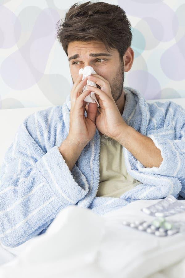 Больной человек дуя его нос в салфетке на кровати дома стоковое изображение rf
