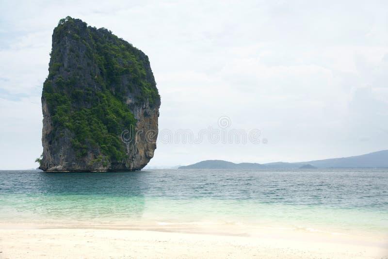 Большая высокая скала утеса заполненная при зеленая вегетация окруженная синью бирюзы покрасила воду океана рядом с тропическим б стоковые фото