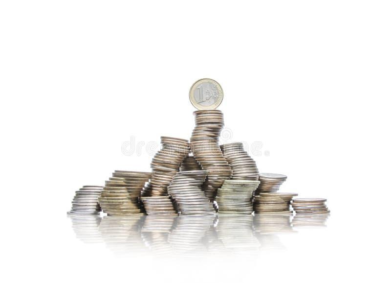 Большая группа в составе изогнутые кучи монеток с одним евро на верхней части стоковые изображения
