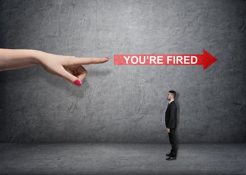 Большая женская рука указывая на красную стрелку с & x27; you& x27; words& увольнянное re x27; над малым предпринимателем стоковое изображение rf
