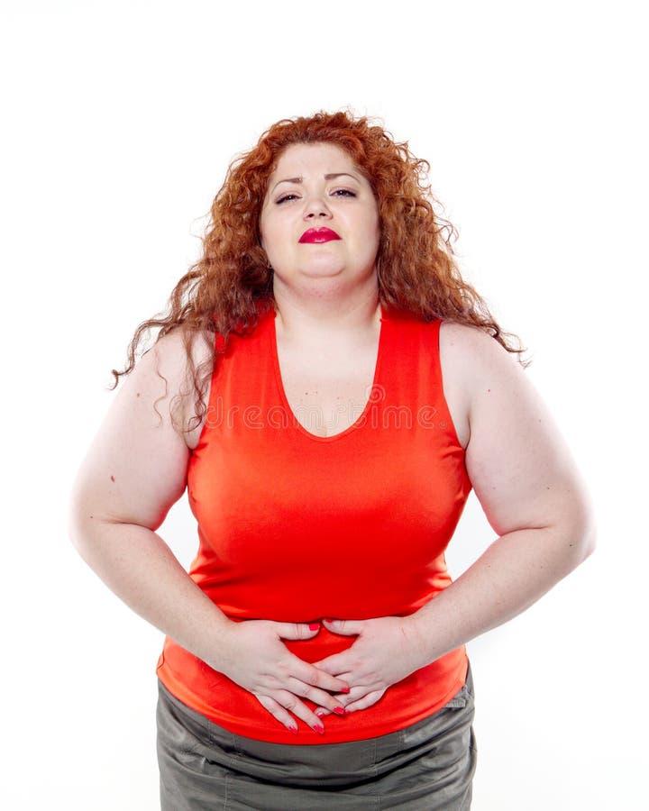 Большая женщина с красной губной помадой и большой болью в животе, плохим настроением стоковое фото
