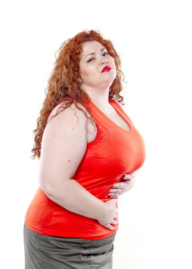 Большая женщина с красной губной помадой и большой болью в животе, плохим настроением стоковые фотографии rf