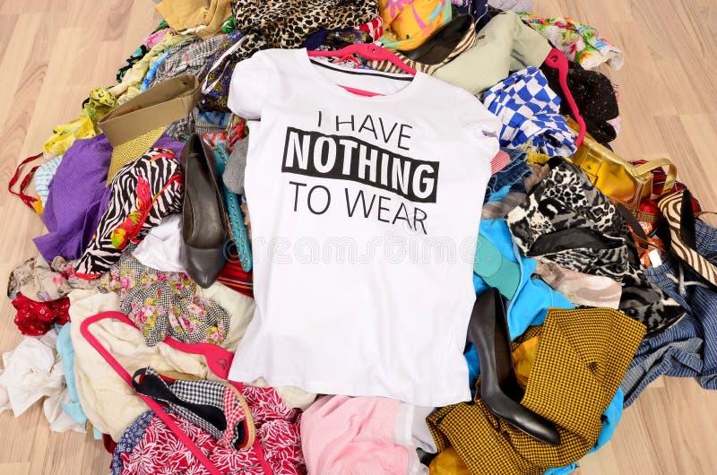 Большая куча одежд брошенных на том основании при футболка говоря n стоковая фотография rf
