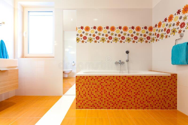 Большая оранжевая ванна в милой современной ванной комнате стоковая фотография