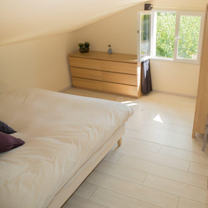 Большая удобная двуспальная кровать в элегантной классической спальне с окнами стоковая фотография