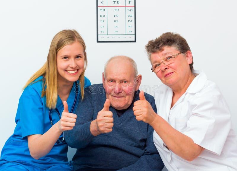 Большие пальцы руки вверх от пожилого человека и его попечителей стоковое фото rf