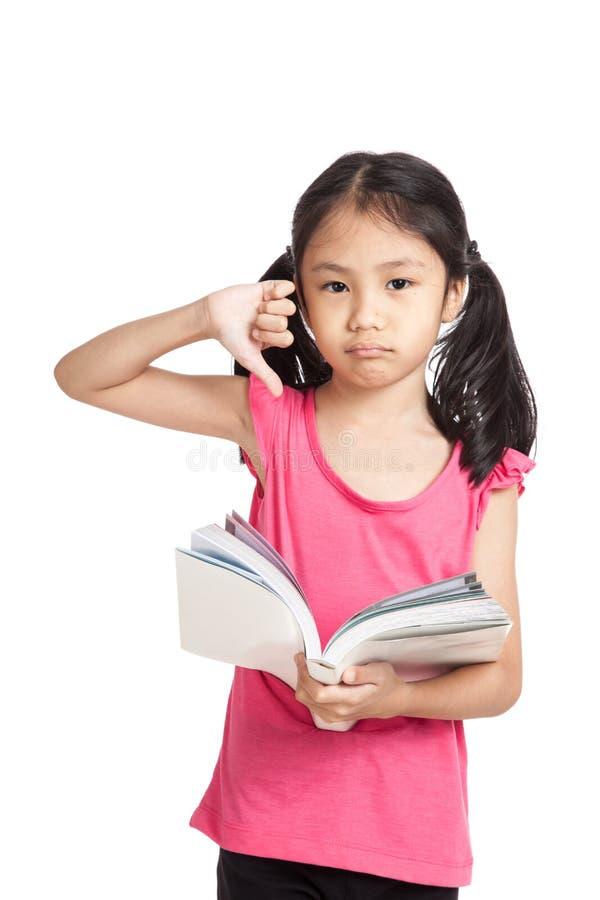 Большие пальцы руки выставки маленькой азиатской девушки несчастные вниз прочитали книгу стоковая фотография rf