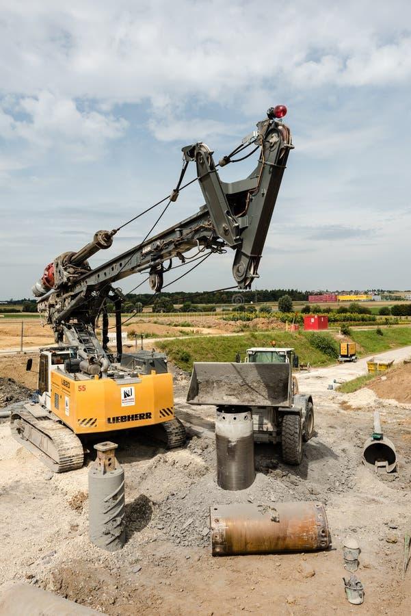 Большие роторные сверло и экскаватор на строительной площадке стоковая фотография