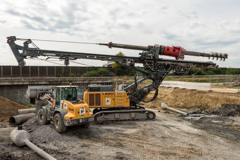 Большие роторные сверло и экскаватор на строительной площадке стоковые фотографии rf