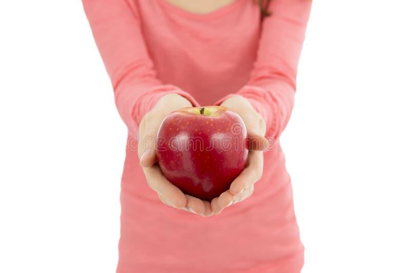 Большое красное яблоко в женских руках стоковые изображения