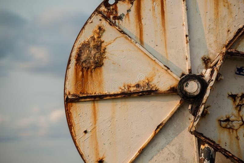 Большое стальное ржавея снаряжение колеса используемое для того чтобы потянуть в рыболовных сетях o стоковая фотография