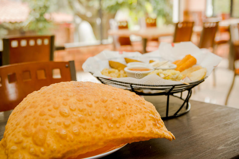 Большое empanada на деревянном столе рядом с корзиной  стоковая фотография