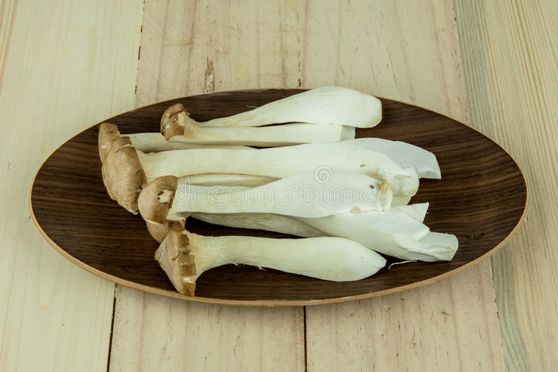 Большой гриб устрицы (гриб Eryngii Pleurotus) украшенный на плите над деревянной предпосылкой стоковое изображение rf