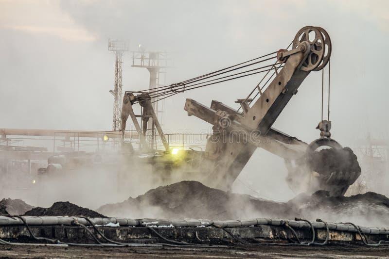 Большой ковшевой экскаватор работает в сбросе пыли outdoors стоковая фотография