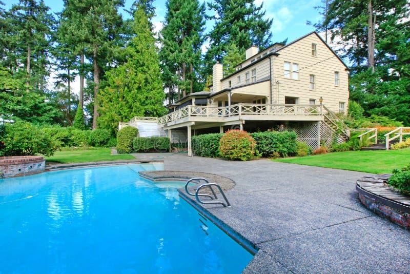 Большой коричневый экстерьер дома с садом лета и плавательным бассеином стоковые фотографии rf