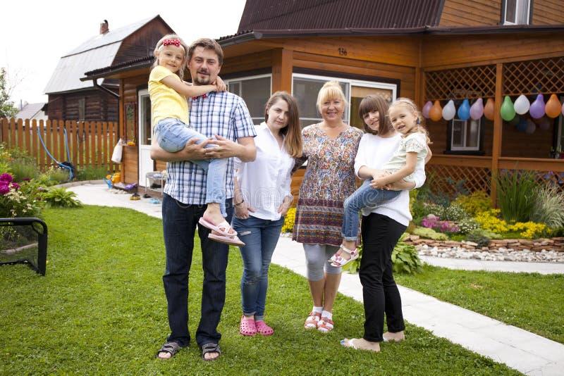 Большой счастливый портрет семьи на предпосылке загородного дома стоковое изображение