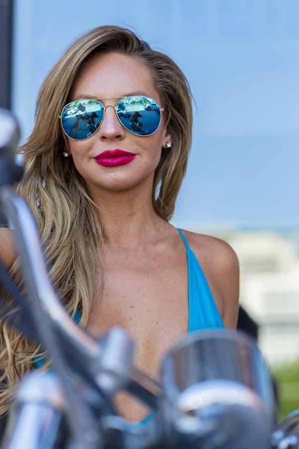 Бразильская белокурая модель бикини представляя Outdoors с мотоциклом стоковые изображения rf
