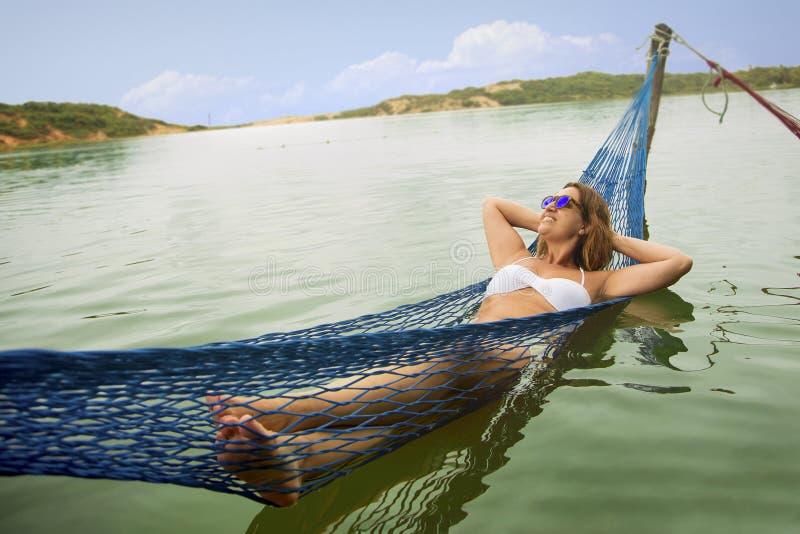 Бразильская женщина на гамаке в воде стоковые изображения rf