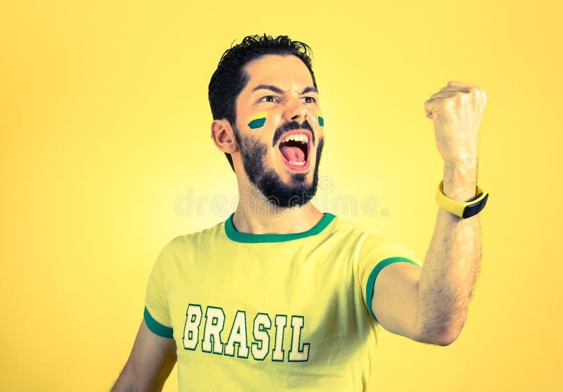 Бразильский сторонник национальной футбольной команды празднует, ch стоковое изображение