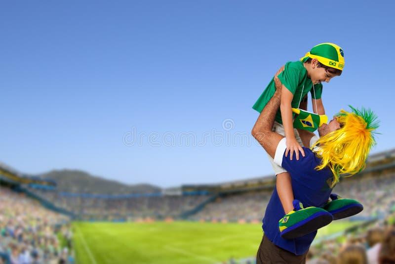 Бразильский вентилятор на стадионе с сыном стоковые изображения