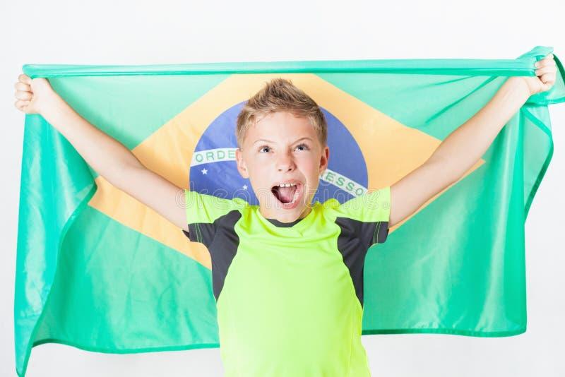 Бразильский мальчик патриота держа флаг Бразилии Чемпионат футбола или футбола стоковые фотографии rf