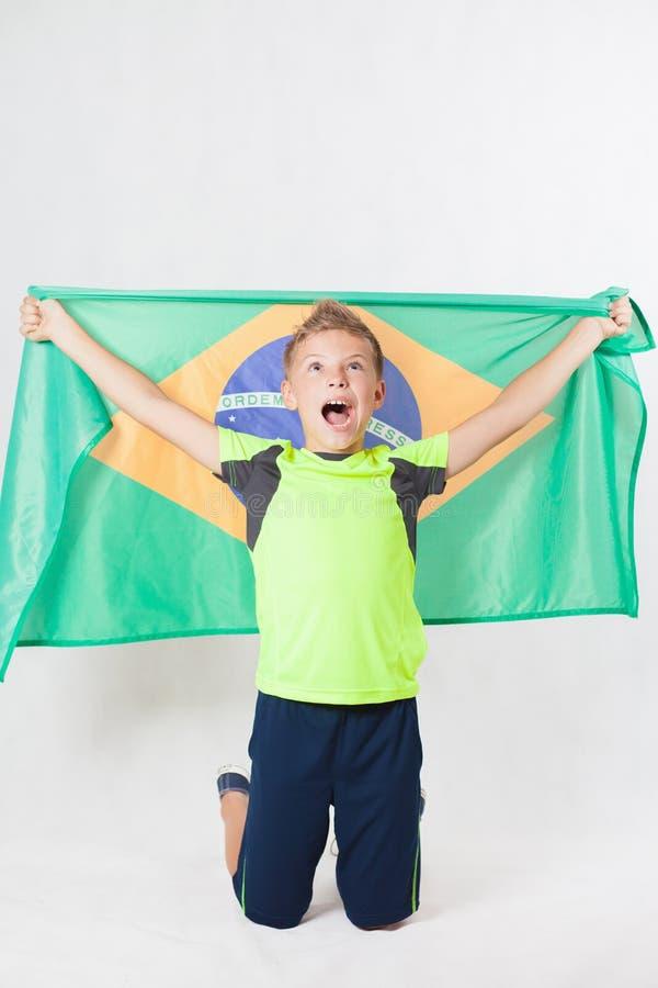 Бразильский мальчик патриота держа флаг Бразилии Чемпионат футбола или футбола стоковая фотография rf