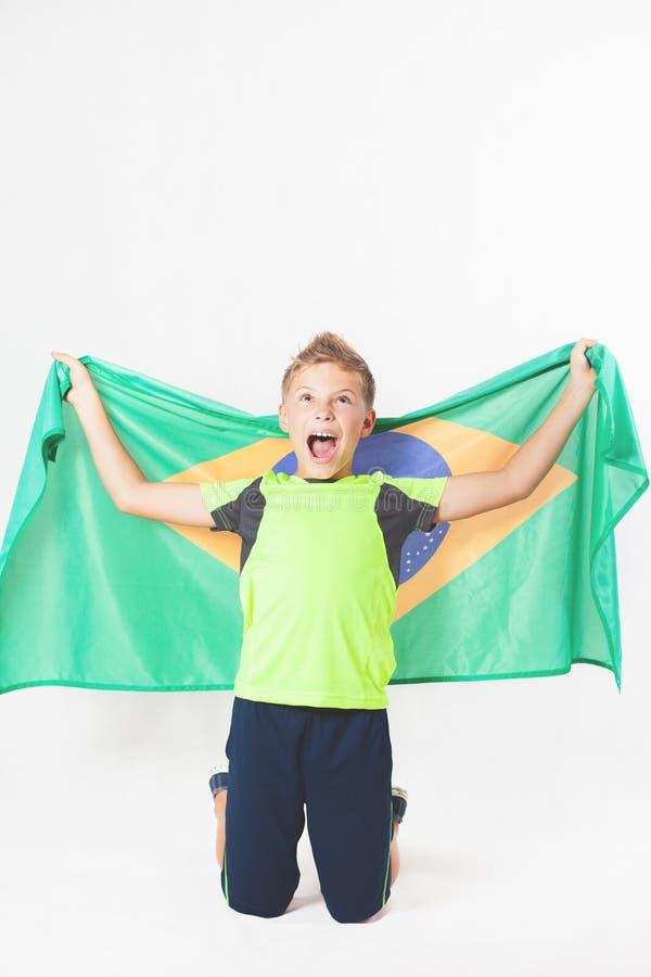 Бразильский мальчик патриота держа флаг Бразилии Чемпионат футбола или футбола стоковые изображения rf