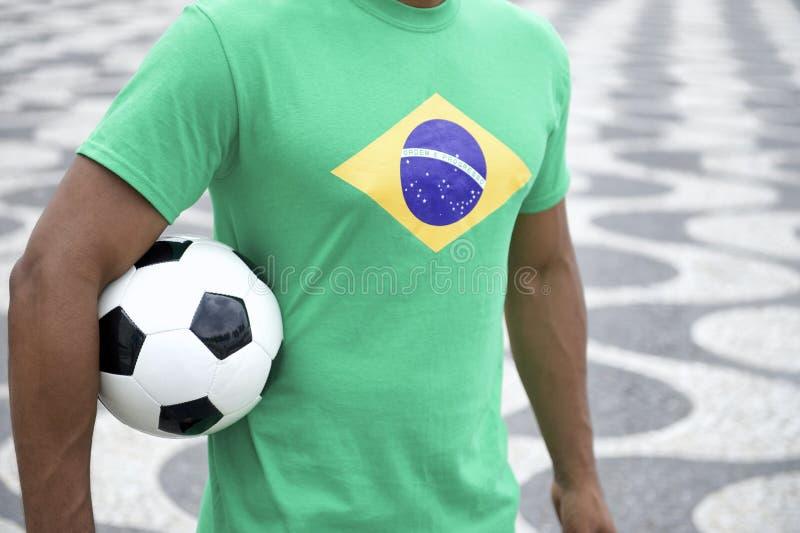 Бразильский футболист в рубашке флага Бразилии держа футбол Рио стоковое фото rf