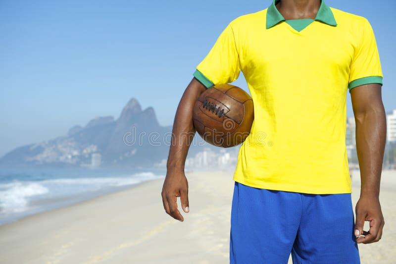 Бразильский футболист держа футбол Рио стоковые фото
