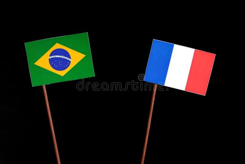 Бразильский флаг с французом сигнализирует изолированный на черноте стоковое изображение